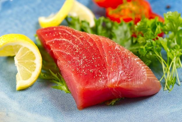Rohes thunfischsteak mit salat und zitrone auf blauem teller