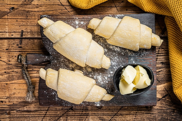 Rohes ungekochtes französisches croissant auf einem holzbrett. hölzerner hintergrund. ansicht von oben.