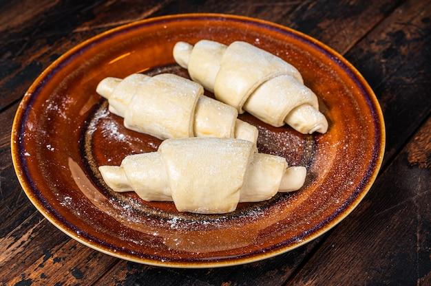 Rohes ungekochtes hausgemachtes croissant auf einem rustikalen teller