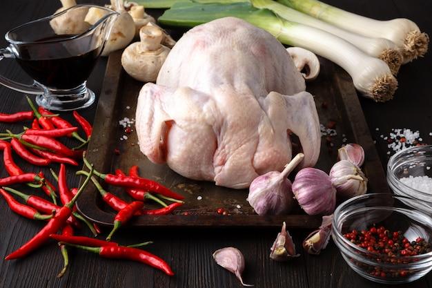 Rohes ungekochtes huhn mit bestandteilen für das kochen