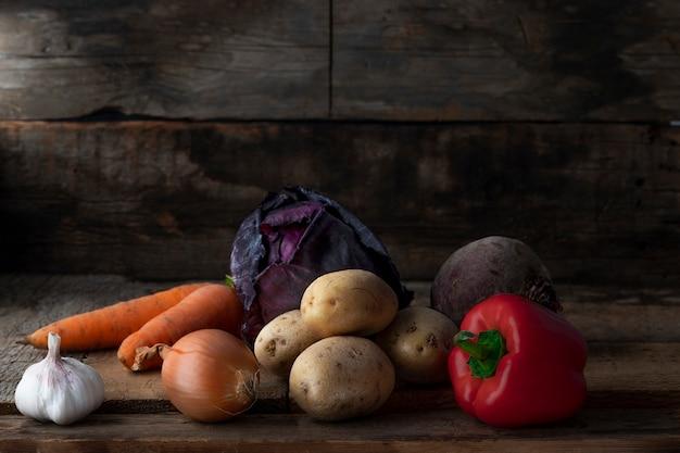 Rohes vegetarisches essen. frischgemüse in einem sellar auf hölzernem hintergrund.