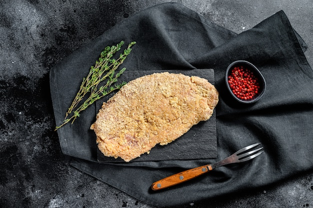 Rohes wiener schnitzel, paniertes steak kochfertig. schwarzer hintergrund. draufsicht