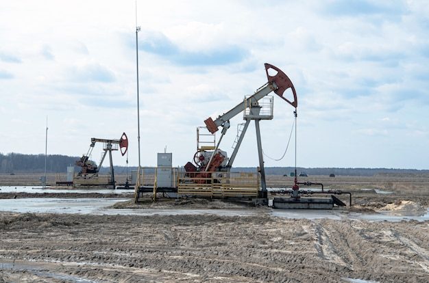 Rohölpumpenheber am ölfeld bei sonnenuntergang. fossile rohölproduktion und ölförderung.
