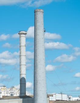 Rohre eines industrieunternehmens vor blauem himmel mit wolken. schornstein ohne rauch