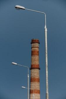 Rohrkraftwerk zwischen laternen auf dem himmelshintergrund.