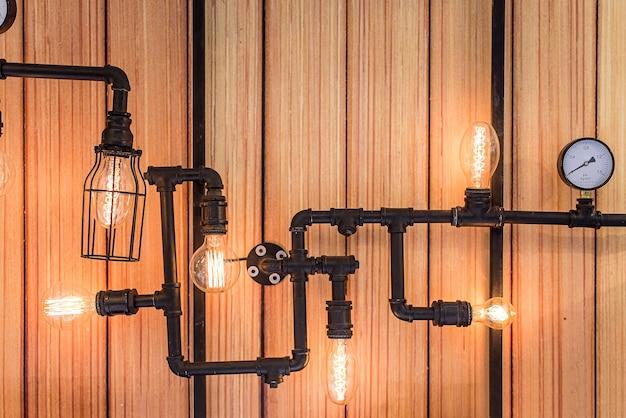Rohrleitung mit glühlampe auf hölzernem hintergrund und beschaffenheit