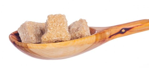 Rohrzuckerstapel mit dem löffel lokalisiert auf weiß