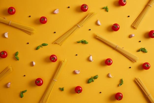 Rohstoffe für die herstellung von nudeln. spaghetti, tomaten, knoblauch und basilikumblätter. kräuter und gewürze für italienisches essen. vorbereitung des essens. gelber hintergrund. kochen hausgemachte köstliche küche. essen