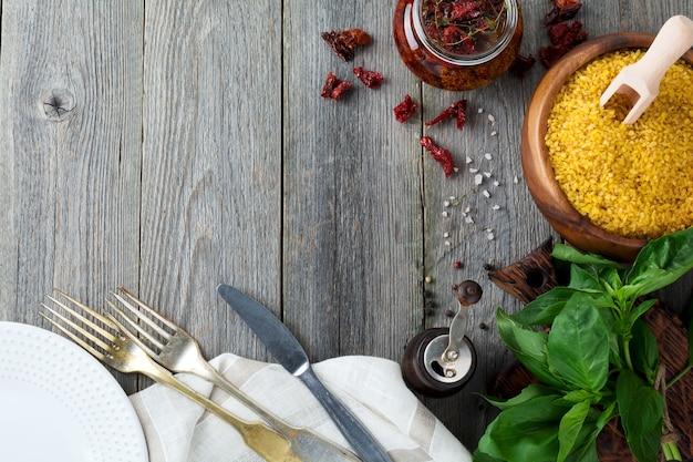 Rohstoffe für die zubereitung von mahlzeiten bulgur, sonnengetrocknete tomaten, paprika, basilikum, keramikplatte, gabel, serviette auf alter holzoberfläche. rustikaler stil. platz kopieren. ansicht von oben. selektiver fokus.