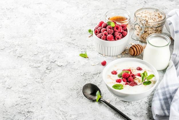 Rohstoffe für gesundes frühstück des sommers, getreide (hafer), frische himbeere