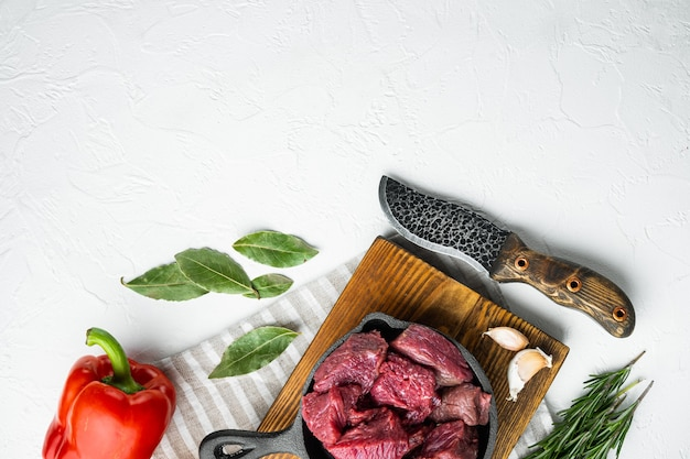 Rohstoffe für gulasch. frisches, rohes, gehacktes rindfleisch in einer gusseisernen pfanne auf weißem stein