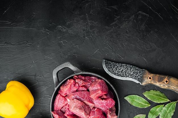 Rohstoffe für gulasch. frisches rohes gehacktes rindfleisch mit süßem paprika, in gusseiserner pfanne, auf schwarzem steintisch, draufsicht flach gelegt