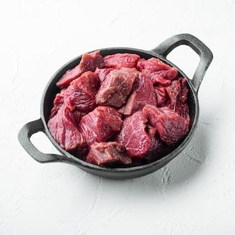 Rohstoffe für gulasch. frisches, rohes, gehacktes rindfleischset in einer gusseisernen pfanne auf einer weißen steinoberfläche im quadratischen format