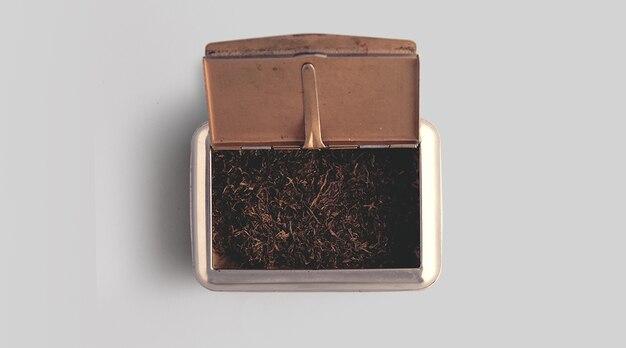 Rohtabak in einer box vor weißem hintergrund. top-up-ansicht