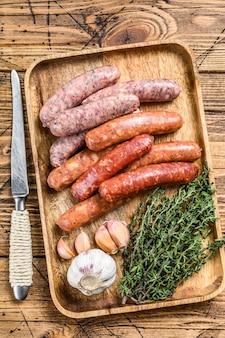 Rohwürste variation, rind- und schweinefleisch. holztisch. draufsicht.