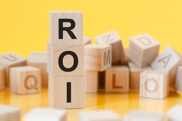 Roi - abkürzung für return on investment - geschrieben auf einem holzwürfel