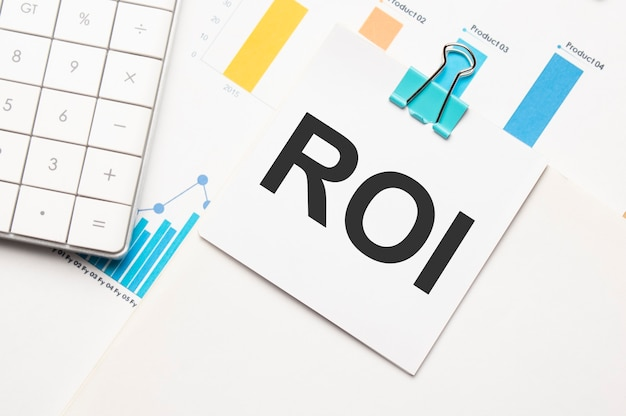 Roi-textkonzept. büroarbeitsplatztisch mit taschenrechner, grafiken, berichten und dem text budget 2021 auf einem kleinen stück papier auf mehrfarbigem hintergrund.