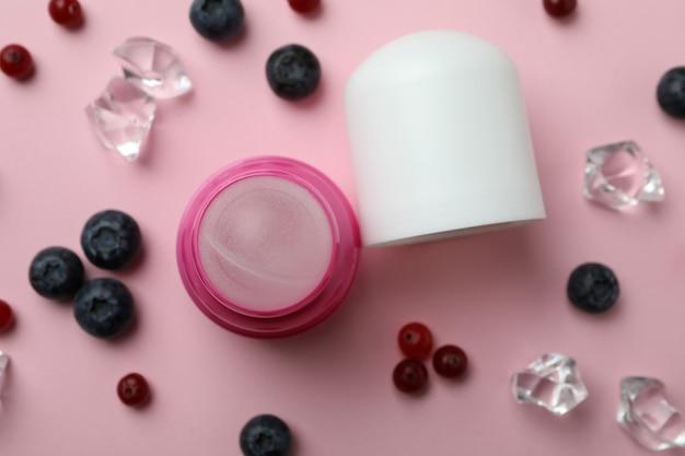 Roll-on deodorant, eiswürfel und beeren auf rosa hintergrund