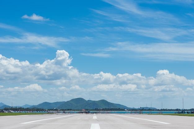 Rollbahn für flugzeuglandung oder -start im blauen himmel mit wolke