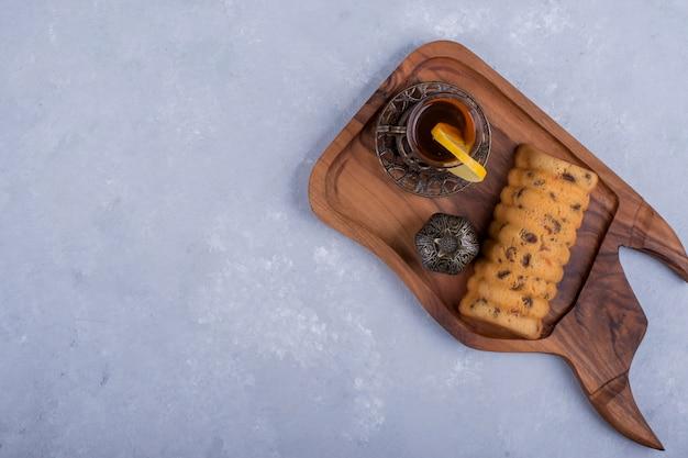 Rollcake serviert mit earl grey tea auf einer holzplatte