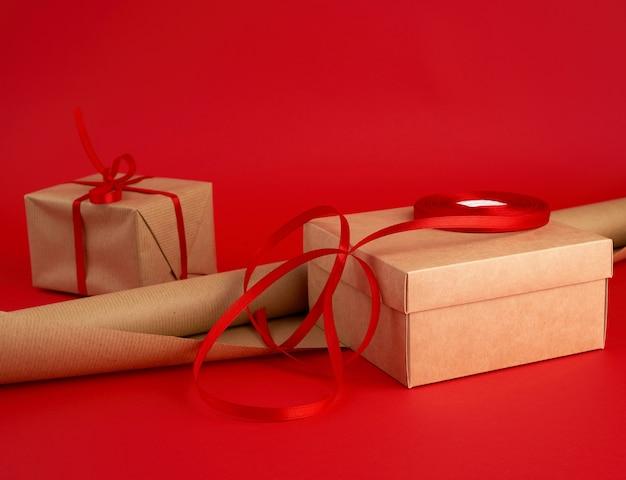 Rolle braunes papier zum verpacken, eine rolle rotes band und ein verpacktes geschenk in braunem kraftpapier auf rot