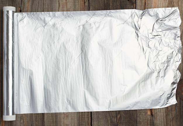 Rolle der grauen folie für das backen und verpacken des lebensmittels auf einer holzoberfläche