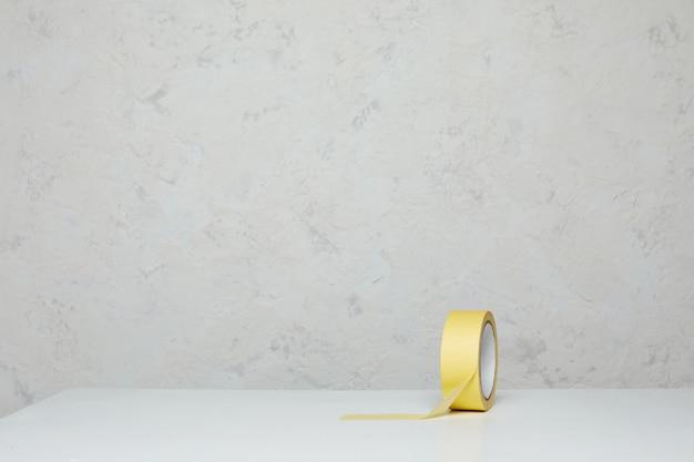 Rolle des gelben papierabdeckbandes auf holztisch