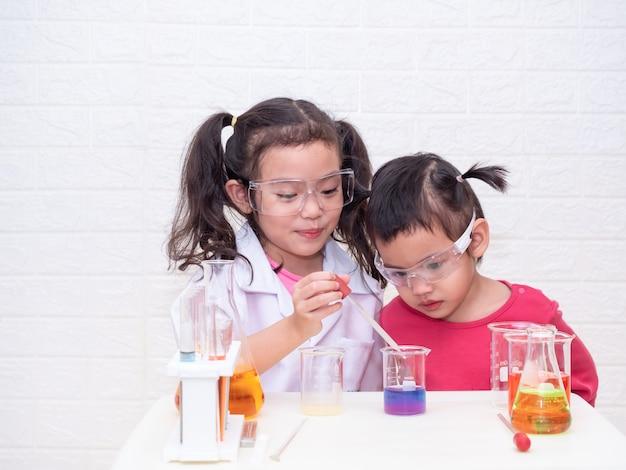Rolle des kleinen asiatischen netten mädchens zwei, die einen wissenschaftler mit ausrüstung auf weißer tabelle spielt.