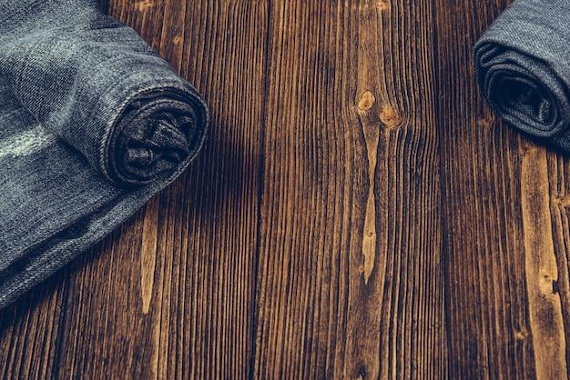 Rolle frayed jeans oder blue jeans denim auf dunklem holz