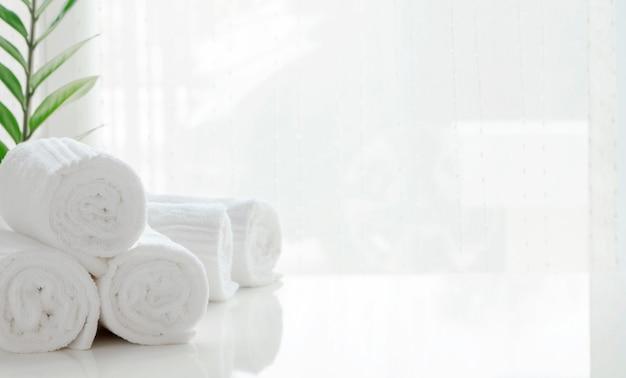 Rolle sauberer handtücher und zimmerpflanze auf weißem tisch mit hellem hintergrund.