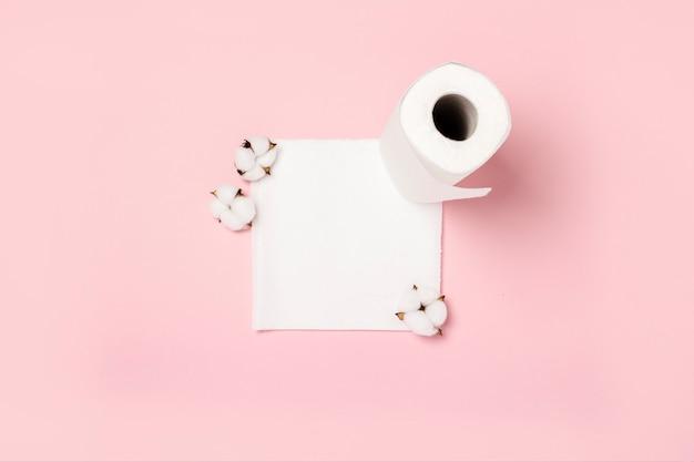 Rolle von papiertüchern und von baumwollblumen auf einer rosa oberfläche. konzept ist 100 naturprodukt, zart und weich. flachgelegt, draufsicht