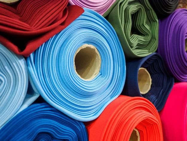 Rollen aus hellem mehrfarbigem stoff nahaufnahme. stoffspulen stehen in den regalen im laden.