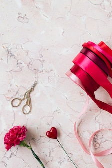 Rollen aus rotem band auf rosa marmorhintergrund