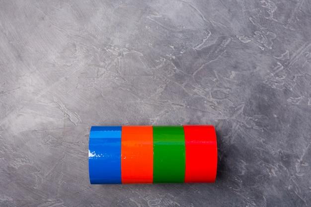 Rollen des farbigen klebebandes auf grauem hintergrund. freiraum. speicherplatz kopieren.