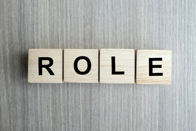 Rollen-geschäftswort begrifflich mit hölzernem würfelblock auf tabellenhintergrund