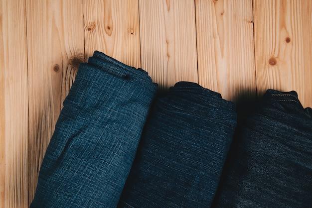 Rollen sie ausgefranste jeans oder blue jeans-denimkollektion auf holz