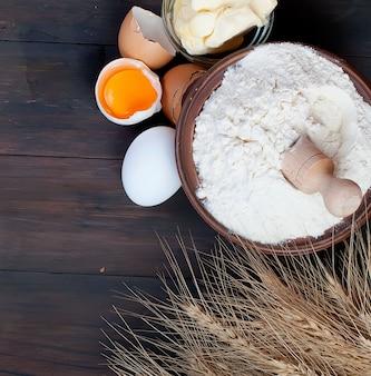 Rollen sie mit den mehleierohren des weizens und der butter auf lebensmittel- und getränkkonzept des hölzernen brettes der weinlese