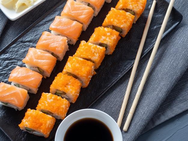 Rollen sie philadelphia und kalifornien auf einem schwarzen teller. ansicht von oben, flach. ingwer, wasabi und sojasauce in der nähe. traditionelle japanische küche