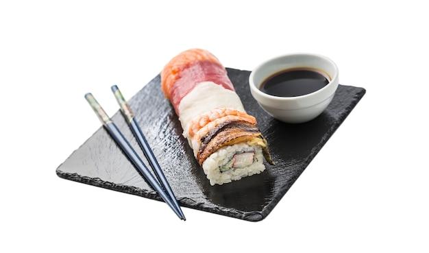 Rollen sie sushi gold kalifornien mit stäbchen und sojasauce auf weißem hintergrund.