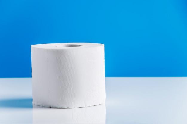 Rollen toilettenpapier auf einem blauen hintergrund. panikkauf von wesentlichen gütern. die coronavirus-epidemie.