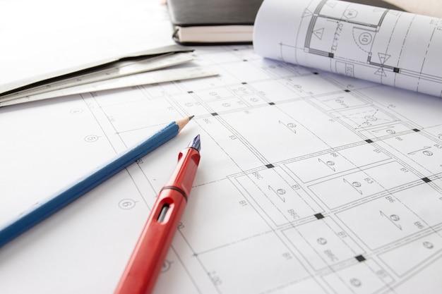 Rollen von architekturentwürfen und hausplänen auf dem tisch und architektenzeichnungswerkzeugen.