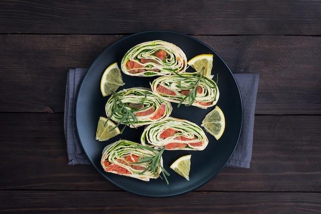 Rollen von dünnem fladenbrot und rotem gesalzenem lachs mit salatblättern auf einem schwarzen keramikteller, dunkler holztisch.