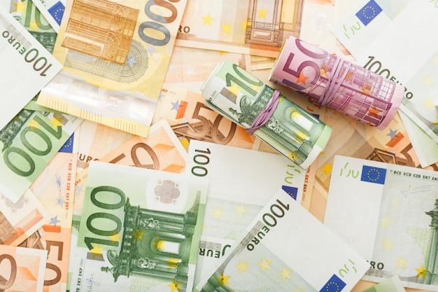 Rollen von euro-banknoten auf verstreutem euro-geld