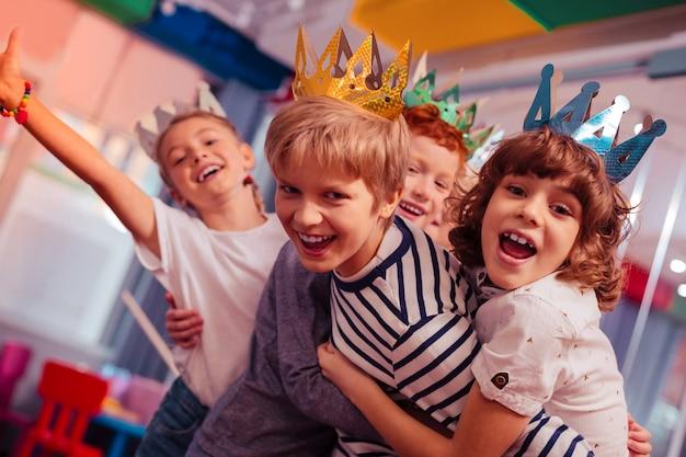 Rollen während des spiels. erfreute kinder fühlen sich glücklich, während sie gemeinsam geburtstag feiern