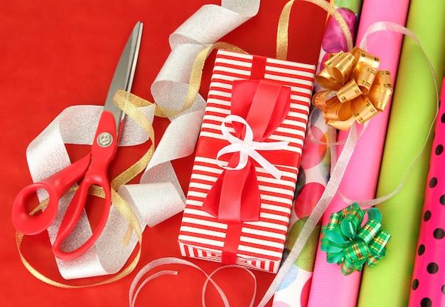 Rollen weihnachtspapier mit bändern, schleifen auf farbigem hintergrund