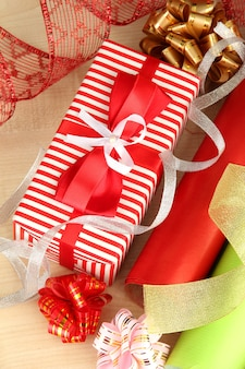 Rollen weihnachtspapier mit bändern, schleifen auf holzuntergrund
