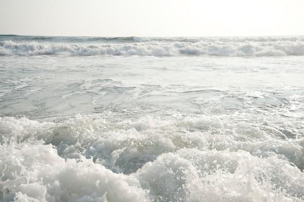 Rollende meereswellen parallel zum horizont an einem bewölkten tag