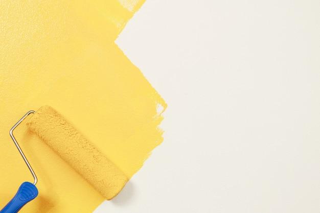 Roller brush painting, arbeiter malerei auf oberflächenwand malerei wohnung, renovierung mit gelber farbe.