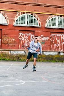 Rollerskating des jungen mannes am gericht draußen