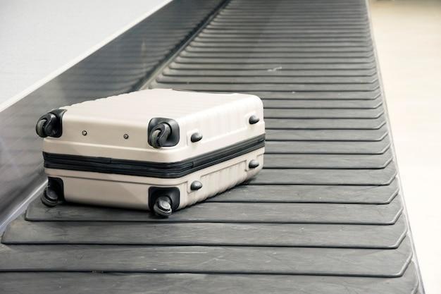Rollkoffer auf einem gepäckgurt am flughafenterminal.